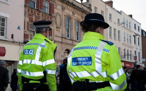 Woman police community support officer walking through Hereford City Centre, UK. Rear view of female CSO with male colleague.