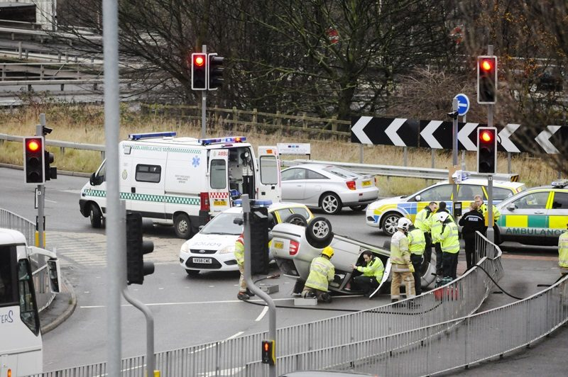 Stoke-on-Trent, England - December 20, 2011: Emergency services attend the scene of a road traffic accident where a car has overturned at a junction to a roundabout.