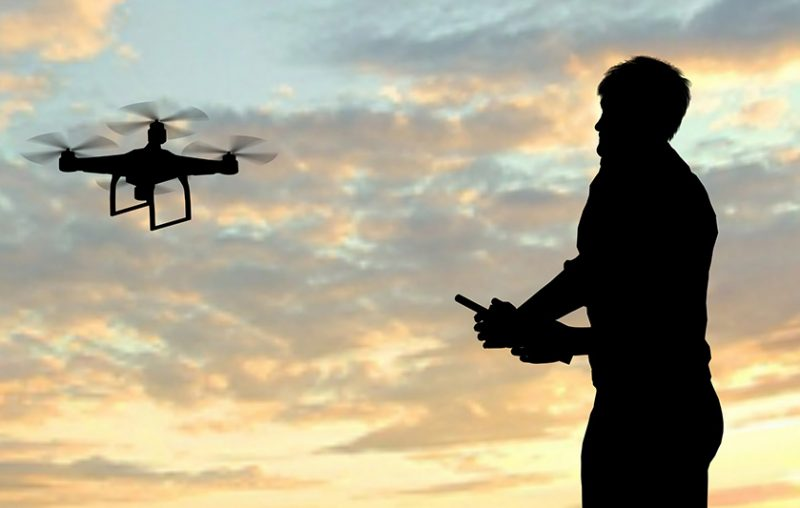 man operating flying drone