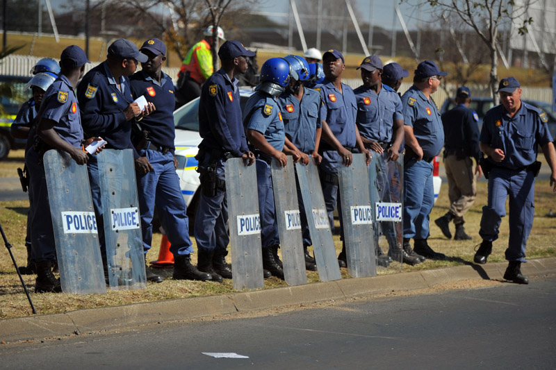 Armed South African police officers of the JMPD with riot shields.